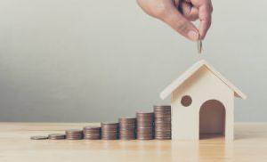 積み重ねられたコインと家の模型