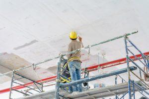天井を塗装する人
